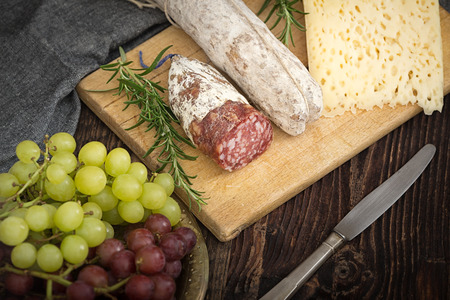 High - quality cheese with salame, grapes, tomatoes, rosemary on the wooden plate.