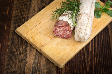 High - quality dried salami with rosemary and basil on the wooden plate.