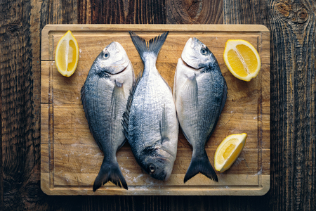 Gilthead seabream (Sparus aurata) ready to bake with lemon, salt and chive. Reklamní fotografie
