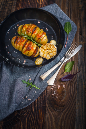 Baked hasselback potaoes  wiht bacon, sausage,cheese and rosemary