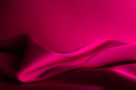 Shiny wine - red  satin curved in various lines. Reklamní fotografie