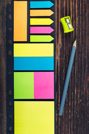 Bunch of colored sticky notes on the wooden background.