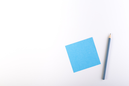 Blue blank sticky note with ordinery pencil.