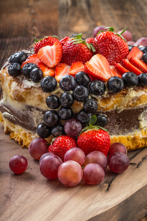 Outstanding fruit cake with strawberries, blueberries, grapes and chocolate. Celebratory tart.