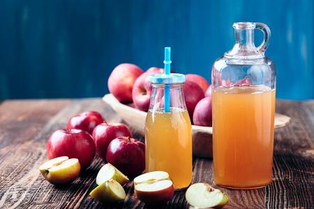 Two bottle fresh organic apple cider or apple juice on the old a wooden table. Reklamní fotografie