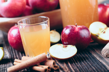 Fresh organic apple cider or apple juice with with cinnamon on the old a wooden table.