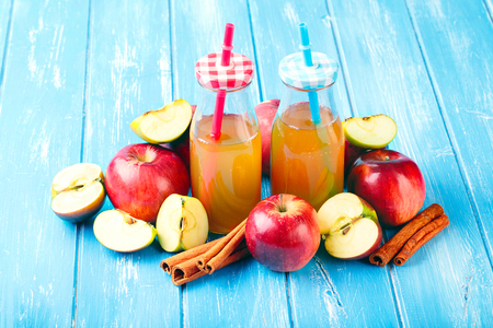 Two bottle fresh organic apple cider or apple juice with with cinnamon on the blue background.
