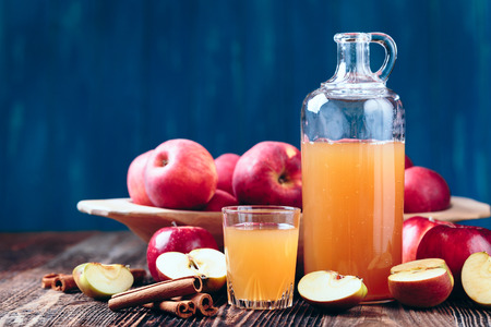 Fresh organic apple cider or apple juice with cinnamon on the old a wooden table. Reklamní fotografie