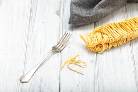 Fresh homemade Italian pasta on a table with fork Reklamní fotografie
