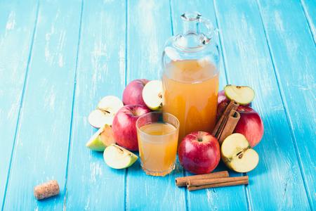 Fresh organic apple cider or apple juice with on the blue background. Reklamní fotografie