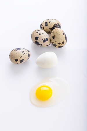 Organic quail eggs on the white background. Boiled and broken egg.