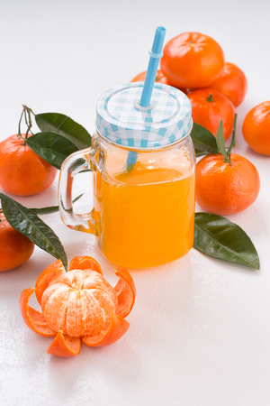 Fresh tangerines on a white background. Juicy mandarins with green leaves. Glass mug with handle.Vertical picture.