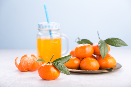 Fresh tangerines on a white table. Juicy mandarins with green leaves. Glass mug with handle. Stok Fotoğraf