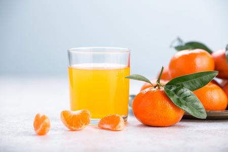 Glass of mandarin juice. Juicy tangerines with green leaves. Stok Fotoğraf