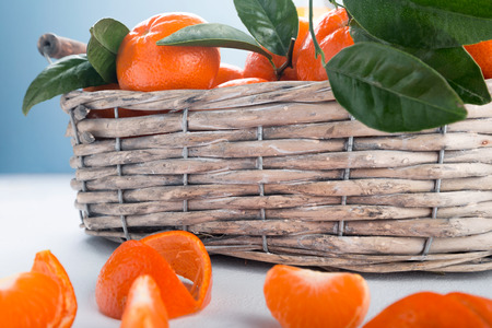 Juicy mandarins with green leaves. Full basket of mandarin on a white background. Imagens