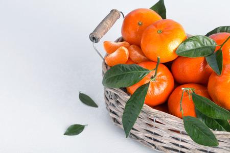 Juicy mandarins with green leaves. Full basket of mandarin on a white background. Stok Fotoğraf