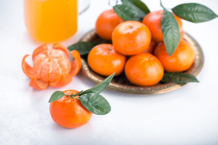 Fresh tangerines on a white background with glass jar. Juicy mandarins with green leaves. Stok Fotoğraf