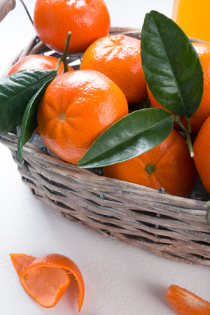 Juicy mandarins with green leaves. Full basket of mandarin on a white background. Vertical picture.