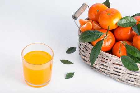 Full basket of mandarin with a glass of juice. Juicy tangerines with green leaves.