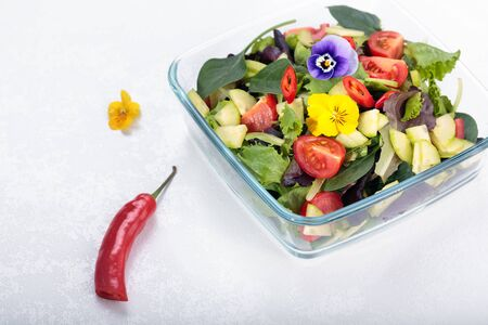 Bowl of vegetable salad with edible flowers and chilli. Stok Fotoğraf