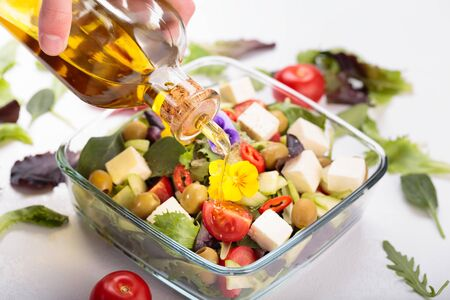 Bowl of vegetable salad with edible flowers and bottle of olive oil. Stok Fotoğraf
