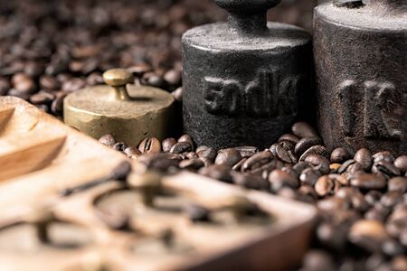 Old rustic metal weights with roasted coffee beans.