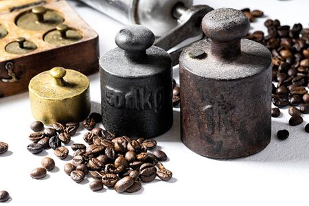 Old rustic metal weights with coffee beans on white background.
