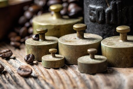 Old rustic metal weights with roasted coffee beans. 스톡 콘텐츠