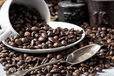 White coffee cup and roasted coffee beans with rustic weight