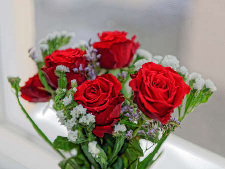 carnations: Bouquet of red roses with white carnations on window Stock Photo