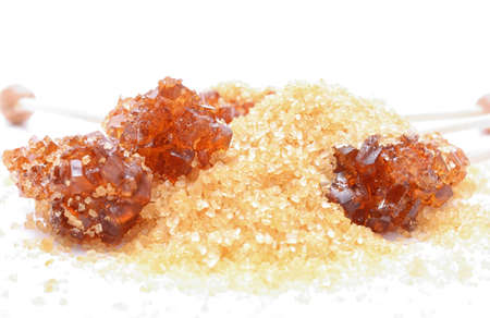 fine cane: Brown sugar crystal on wooden stick and brown granulated sugar on a white background