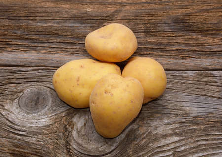 Bunch of potatoes on wooden background photo
