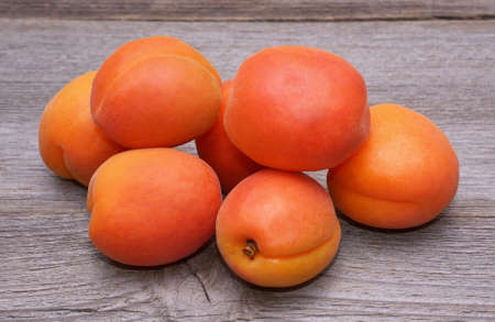 apricot kernels: Fresh apricots on wooden background Stock Photo