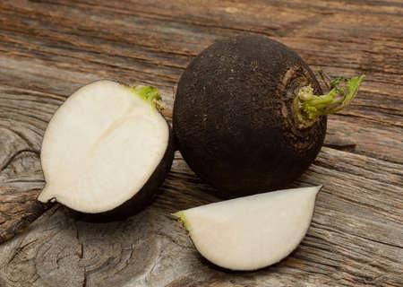 Black radish on wooden background