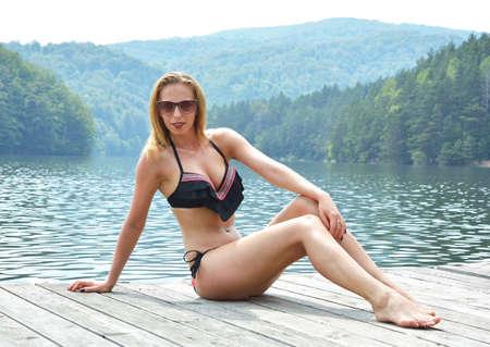 Pretty young woman in bikini posing outdoor in summer