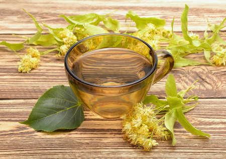 linden tea: cup with linden tea and flowers on wooden background