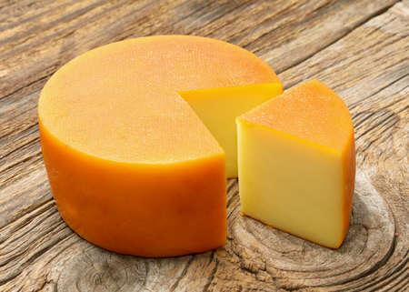 木製の背景にチーズの燻製 写真素材