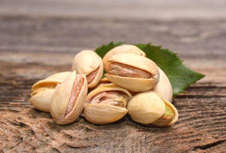 pistachio: Roasted pistachios on wooden background