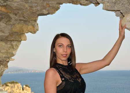 Beautiful woman in black dress posing near Roman ruins with seaside behind