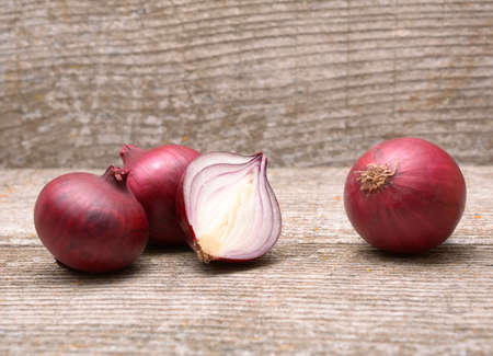 Fresh red onion on wooden background