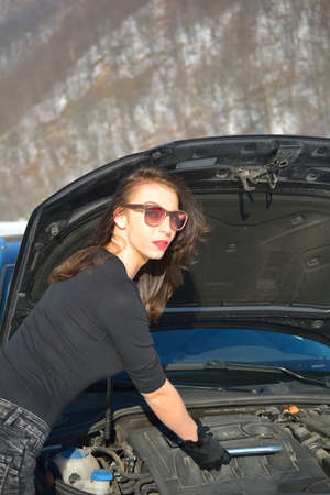 Young beautiful girl trying to repair the car