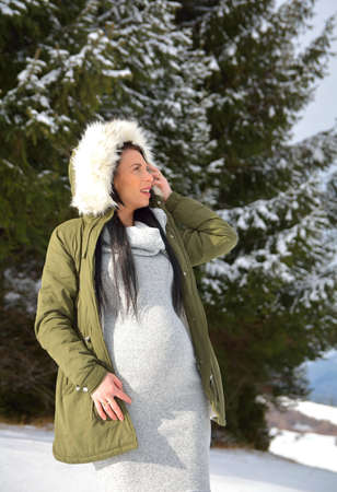 Young happy pregnant woman in snowy nature Standard-Bild - 118557561