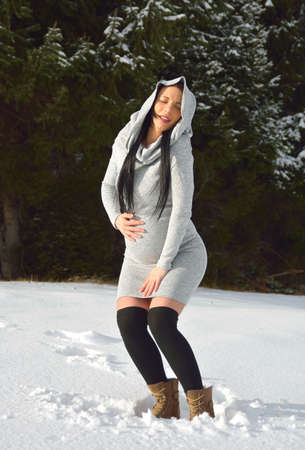 Young happy pregnant woman in snowy nature Standard-Bild - 118557574
