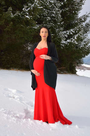 Young happy pregnant woman in snowy nature