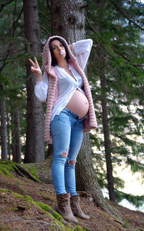 Beautiful pregnant woman. Young happy pregnant woman relaxing and enjoying life in nature Standard-Bild - 118557805