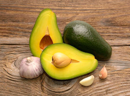 Fresh avocado and garlic on wooden table