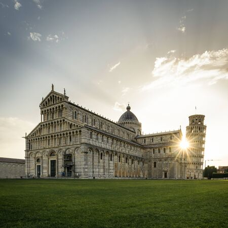 Pisa cathedral and leaning tower at sunrise with spectacular sunburst