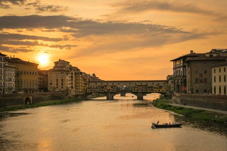 Ponte Vecchio in Florence at sunset with a boat crossing the river Stok Fotoğraf