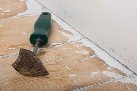 Paint scraper resting on partially stripped wood surface