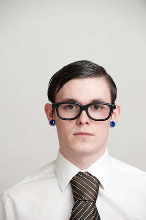 neck tie: Portrait of young man wearing eye glasses white shirt  brown neck tie with pierced ears